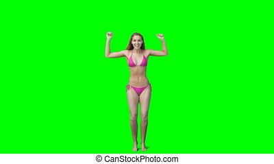 Blonde girl perform a jumping jack against a green screen