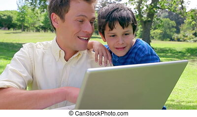 Smiling man using a laptop with his son in a parkland