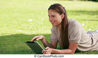 Woman using an eBook in a park - Woman using an eBook while...