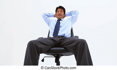 Smiling man sitting on a swivel chair against a white...