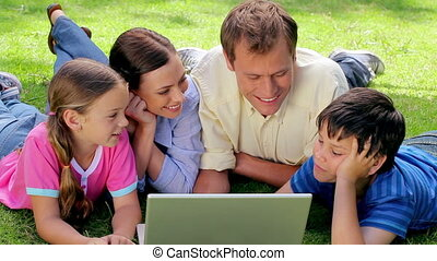 Smiling family lying together while looking at a laptop