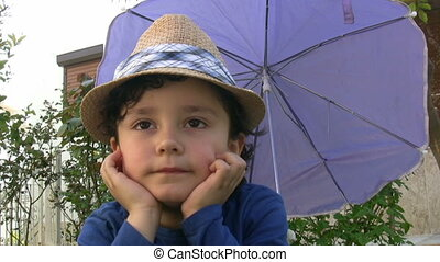 Little boy with sun hat smiling to the camera