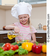 Little girl with oil preparing healthy food on kitchen