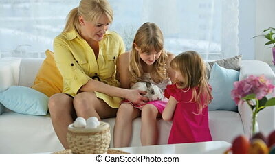 Cutie - Family of three holding and caressing a cute bunny,...