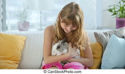 Pet - Teen girl holding a bunny on her knees and caressing...