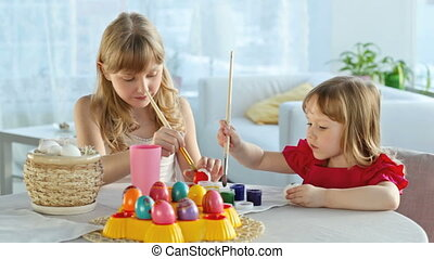Easter preparations - Girls painting eggs getting ready for...
