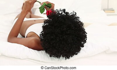 Black haired woman holding a red rose on her bed