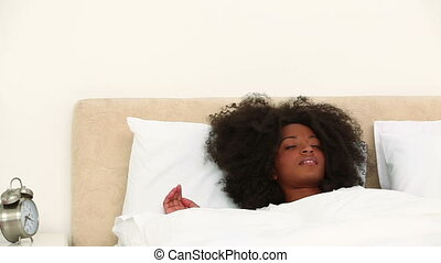 Black woman rubbing her eyes when she wakes up in her...