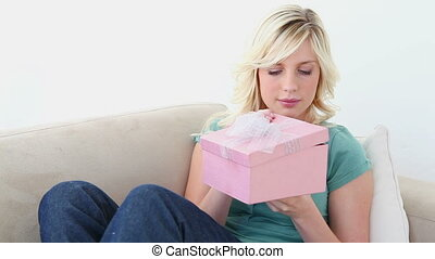 Blonde looking into a gift box on a couch