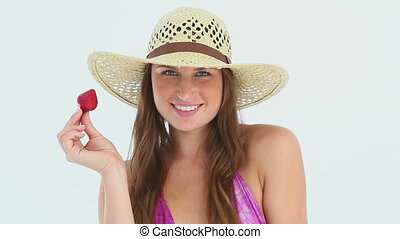 Woman wearing a beach hat eating a strawberry