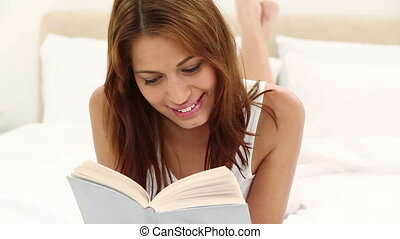 Brunette haired woman reading a novel while lying on her bed