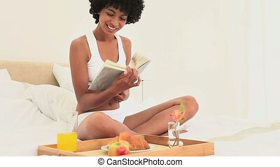 Black haired woman reading a book While having breakfast