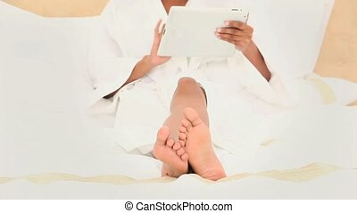 Black haired woman using an ebook on her bed