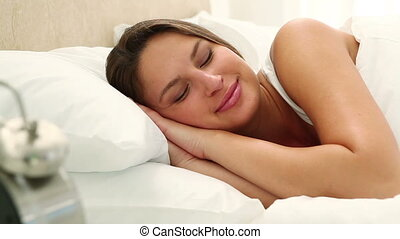 Happy woman checking the time on a clock in her bed