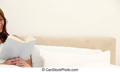 Smiling woman holding a book on her bed