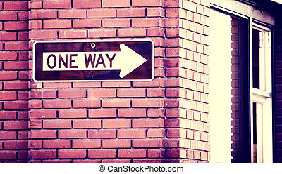 One Way - One way sign on a red brick wall