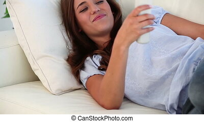 Smiling woman using a remote