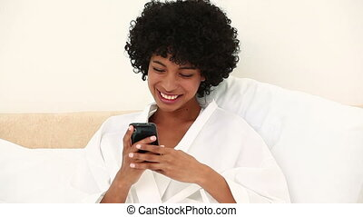 Black haired woman sending a text message