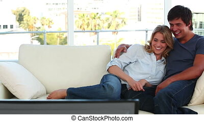 Couple laughing while watching the television