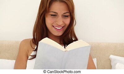 Brunette haired woman reading a novel on her bed