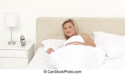 Smiling woman waking up in her bedroom