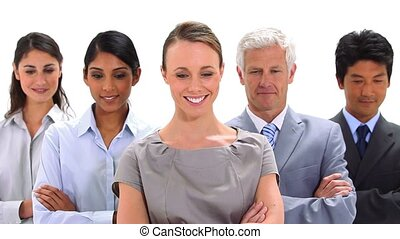 Smiling business people with their arms crossed against a...