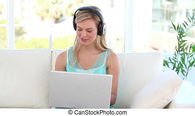 Smiling blonde using a laptop in her living room