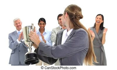 Blonde businesswoman holding a trophy against a white...
