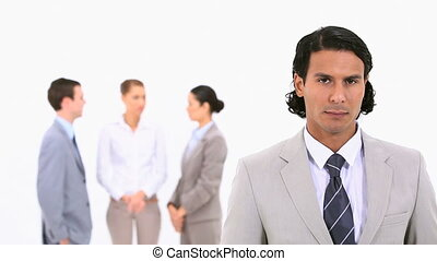 A businessman standing in the foreground against a white...