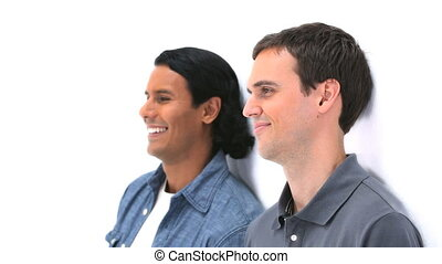 Two men smiling while leaning against a wall against a white...