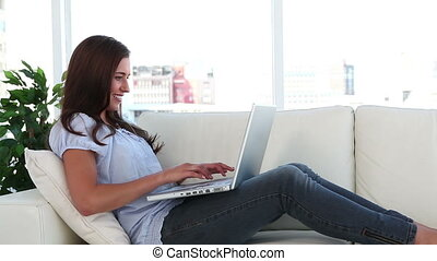 Smiling woman using her laptop in her living room