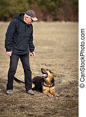 Master and his obedient (German Shepherd) dog