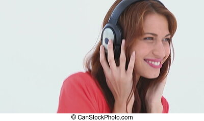 Brunette haired woman dancing with headphones against white...