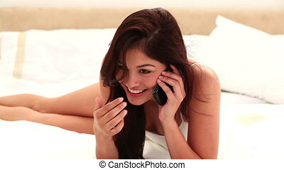 Smiling young brunette using her cellphone