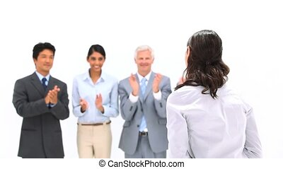 Brunette being applauded by her co-workers against a white...