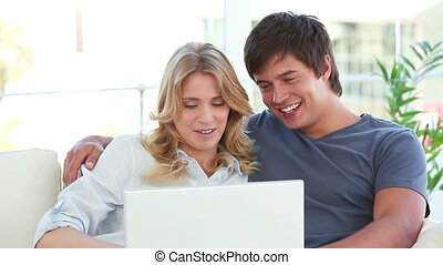 Happy couple talking in front of a laptop in their living...