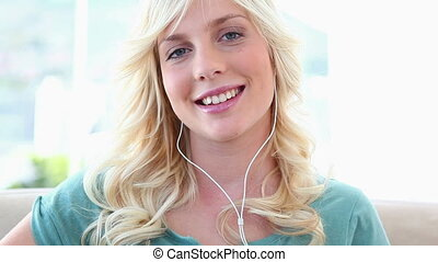 Young blonde woman listening to music on a music player