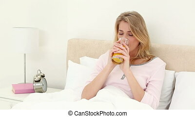 Smiling woman drinking an orange juice in her bedroom