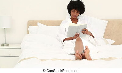 Black haired woman reading a book in bathrobe on her bed