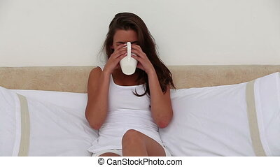 Smiling woman drinking a cup of tea in her bedroom