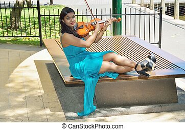 Seated violinist - Violinist sitting down and playing her...