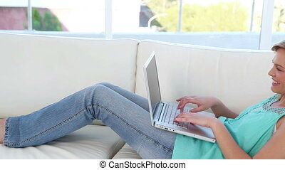 Happy blonde woman using a laptop in her living room