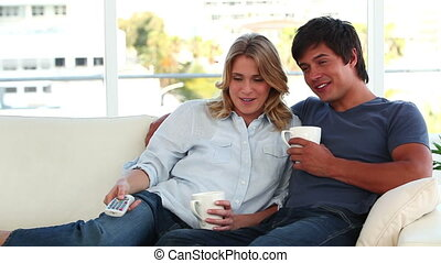 Smiling couple relaxing while watching the television in the...