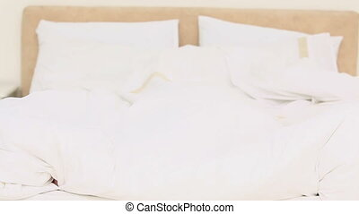 Beautiful young blonde haired woman lifting her duvet