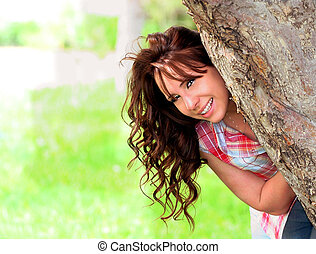 Peek a Boo! - Young lady peeking out from behind a tree