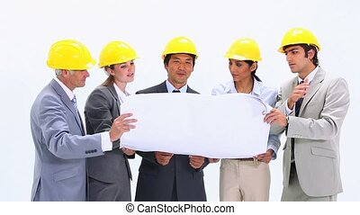 Business people wearing helmets are looking at blueprints -...