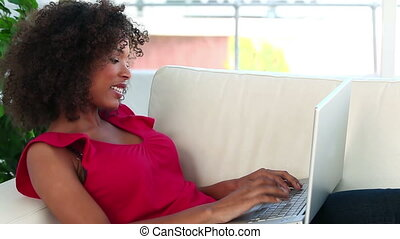 Happy woman writing on a laptop