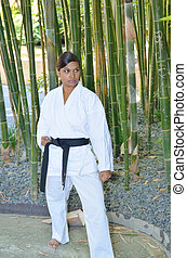 Karate expert in front of a bamboo clump