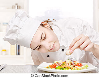 young chef decorating delicious salad - pretty young chef...