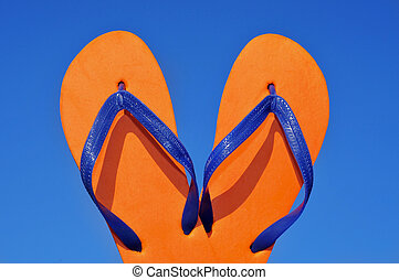 flip-flops - a pair of orange flip-flops over the blue sky